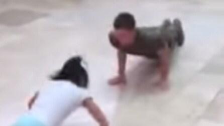 Una ragazza tiene testa al soldato nella sfida di flessioni