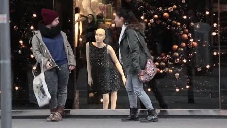 Passanti si fermano davanti alla vetrina di un negozio di lusso non per i vestiti...