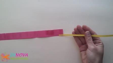 Prende due strisce di carta colorata e quello che realizza è sorprendente
