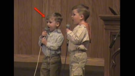 Stavano cantando alla recita scolastica ma il bimbo sulla sinistra fa ridere tutti