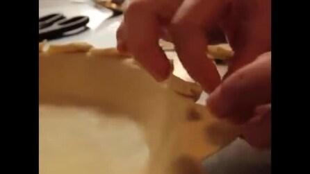 Decorare il bordo della crostata usando una pinza o una forchetta