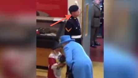 La bambina porge i fiori alla regina ma guardate attentamente la guardia