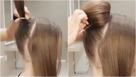 Realizza una coda alta, poi raccoglie i capelli: un'acconciatura elegante e originale