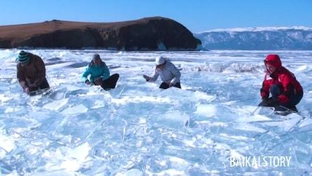 Il lago è completamente ghiacciato, ma quando iniziano a colpirlo con le mani succede qualcosa di incredibile