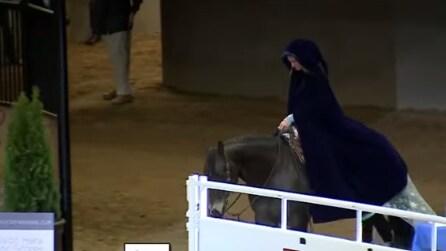 Cavalca il cavallo con un mantello scuro, ma quando lo toglie tutti restano a bocca aperta