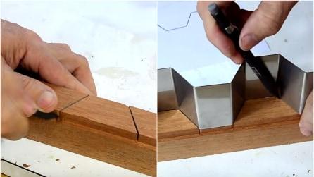 Fa dei tagli al legno e ci infila una strana forma di metallo, creando qualcosa di molto originale