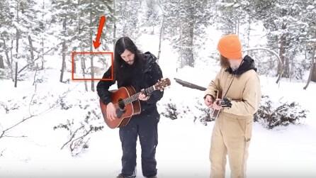 Suonano e cantano sotto la neve: incredibile quello che accade alle loro spalle