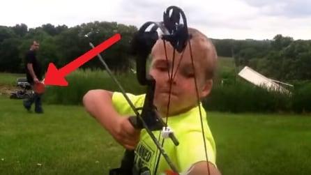 Il papà dietro di lui lancia il piatto e il bambino lo centra in pieno con la freccia