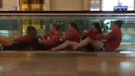 Si siedono sul tappeto mobile dell'aeroporto: quello che fanno lascia tutti a bocca aperta