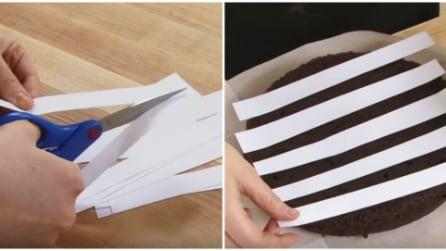 Ritaglia delle strisce di carta e le poggia sulla torta: ecco cosa realizza con lo zucchero