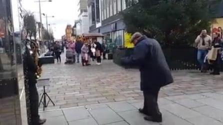 Il nonno felice balla il tip tap in piazza sotto l'albero di Natale