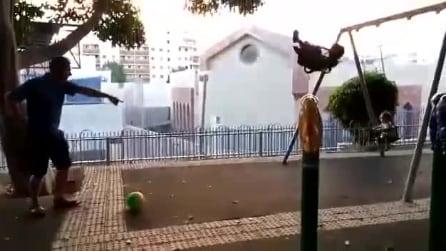 Il figlio si dondola sull'altalena, il papà calcia il pallone e quello che accade è inevitabile