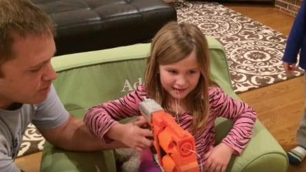 Il papà lega il dentino della figlia alla pistola giocattolo e lei spara