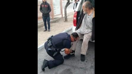 Il poliziotto aiuta il senzatetto ad indossare le scarpe: le immagini diventano virali
