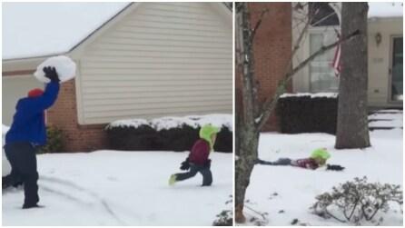 Il papà lancia una palla di neve gigante contro il figlioletto