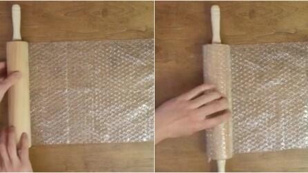 Avvolge la carta imballaggio con bolle attorno al mattarello: la creazione geniale