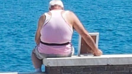 Un anziano signore guarda il mare accanto alla foto della moglie defunta. L'immagine diventa virale