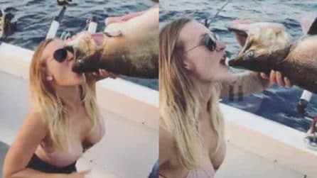 La ragazza beve la birra dalla bocca del pesce: l'assurda scommessa in barca