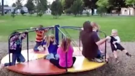 Il padre afferra al volo il figlio che rischia di cadere dalla giostra