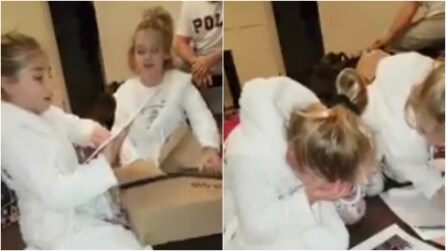 Nella scatola è nascosta una busta: quando la bambina capisce di cosa si tratta, scoppia in lacrime
