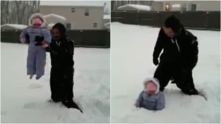 Il papà afferra la bimba e la lascia cadere nella neve: l'insolito gioco