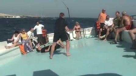 Il mare è agitato e la barca ondeggia molto: i ragazzi si divertono a restare in equilibrio