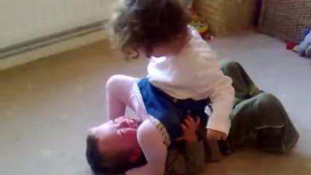La bimba lo blocca a terra sedendosi sopra di lui: la reazione del piccolo è esilarante