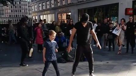 Un bimbo senza un braccio si unisce al numero dell'artista di strada: la tenera performance