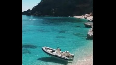 La barca sembra sospesa a mezz'aria: il mare cristallino della Sardegna