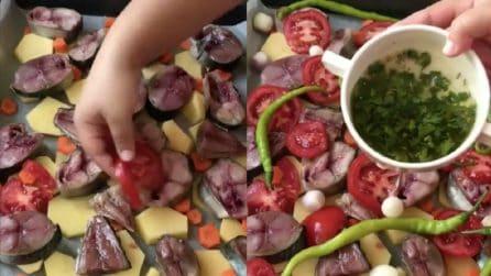 Dispone la verdura e il pesce sulla teglia: un secondo piatto da ristorante