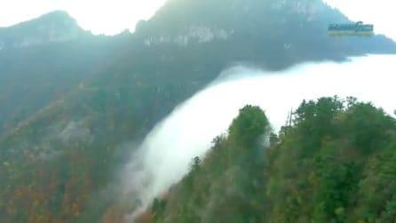 Una cascata di nuvole scende dalla montagna: il raro fenomeno in Cina