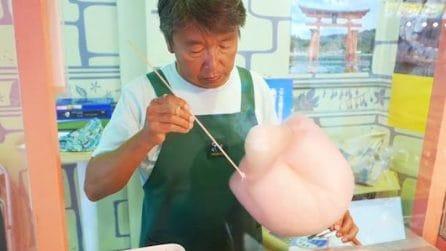 Modella lo zucchero filato con un bastoncino di legno: quello che realizza è fantastico