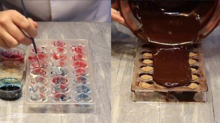 Dipinge gli stampi con colorante, poi aggiunge il cioccolato fuso: quello che prepara è speciale