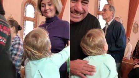 In piedi sulla panca una bimba abbraccia le persone in fila: la dolcissima scena in chiesa