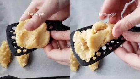 Stende l'impasto sul mestolo e lo farcisce: biscotti originali e ottimi