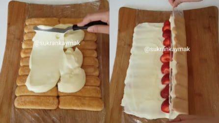 Mette i savoiardi sulla pellicola trasparente e poi aggiunge crema e fragole: un dolce delizioso