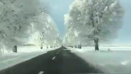 Percorre una strada isolata dove tutto intorno è bianco dopo la nevicata