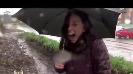 La reporter è in collegamento sotto la pioggia: all'improvviso passa un'auto