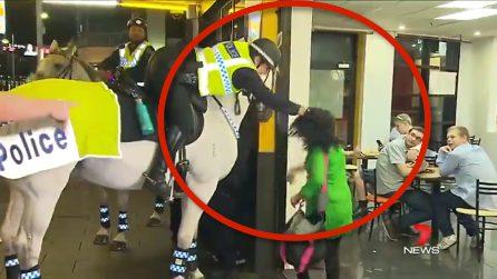 Poliziotto afferra per i capelli una donna e la trascina a terra
