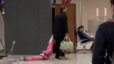 La bimba fa i capricci in aeroporto e il padre la trascina via come fosse una trolley