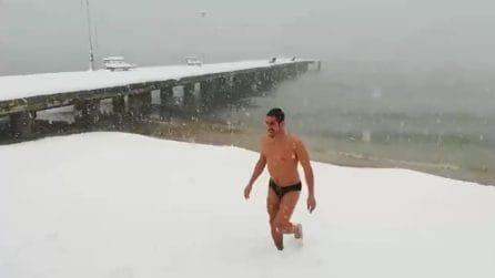 L'uomo si butta in mare con la tempesta di neve: le immagini assurde