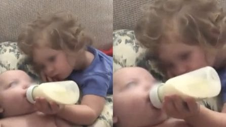La sorellina gli tiene il biberon: la tenera scena tra i due fratellini