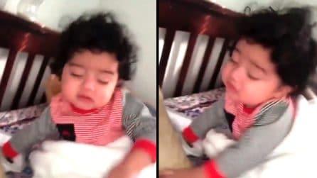 La bambina cerca di alzarsi dal letto ma è tutto inutile