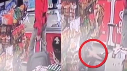 Passeggia nel negozio con il trolley: all'improvviso una mano spunta dalla valigia
