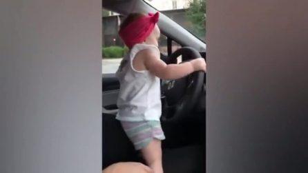 """La bimba in piedi sul sedile, impugna il volante e """"guida"""" l'auto mentre balla"""