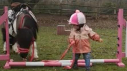 La piccola impara a superare gli ostacoli in compagnia di un amico speciale