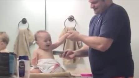 Il padre gli alza le braccia: la reazione del bambino è esilarante