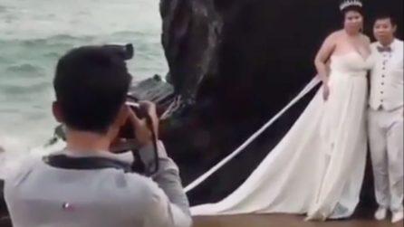 Gli sposi fanno le fotografie a riva, ma il mare è agitato e arriva una violentissima onda