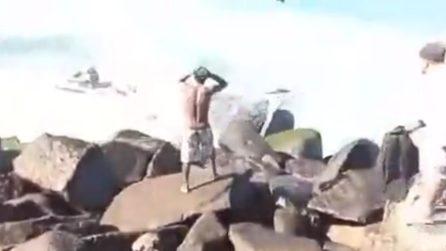 L'uomo sugli scogli si dispera e assiste impotente alla scena
