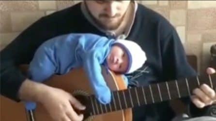 Lo mette sdraiato sulla chitarra e gli suona una dolce melodia: la scena fuori dal comune